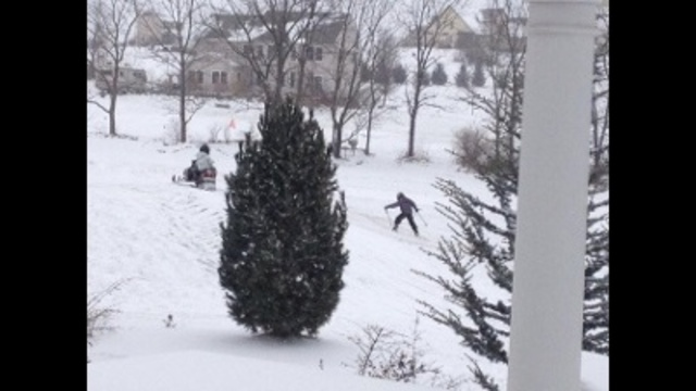 kids snowmobiling & skiing in my Plainfield Township yard_24037788